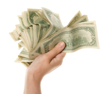 hand with money1 Spring Cleaning Tips That Can Save You Money
