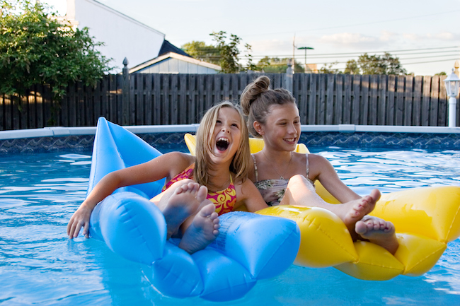 Girls floating together, laughing, and having fun in the swimming pool.