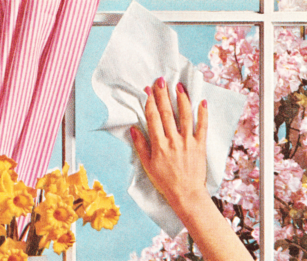 woman's hand cleaning a window