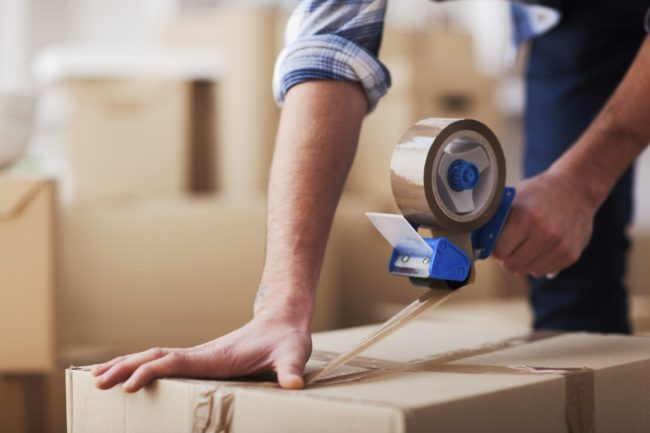 Man packing up moving boxes