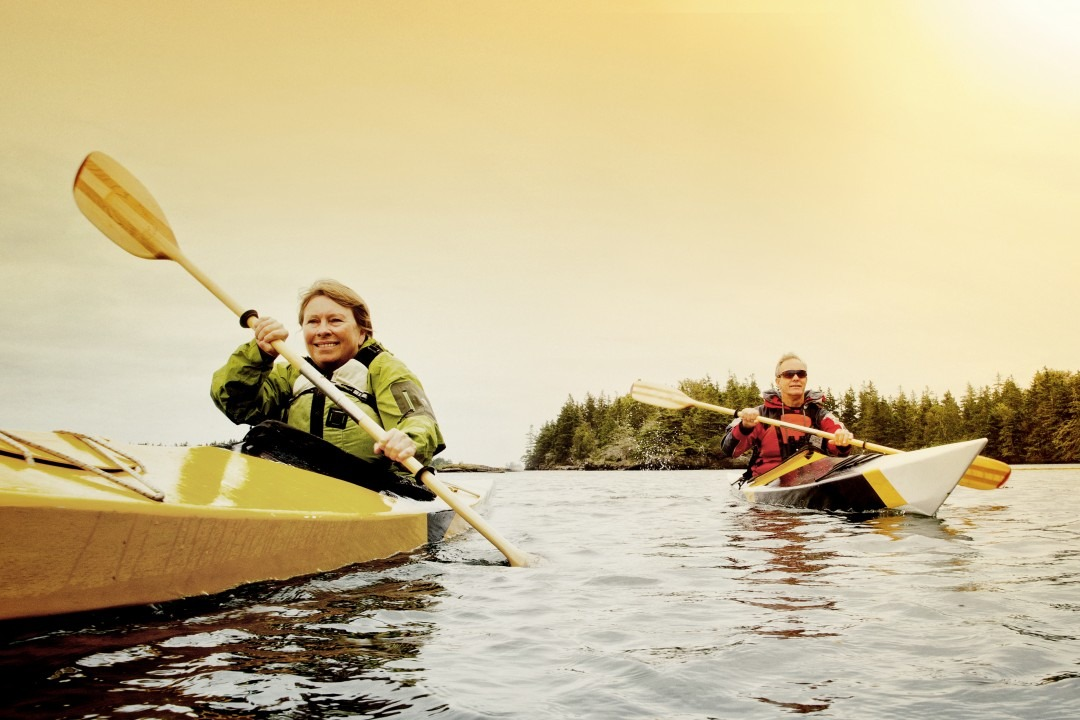 A senior couple kayaking in a lake.