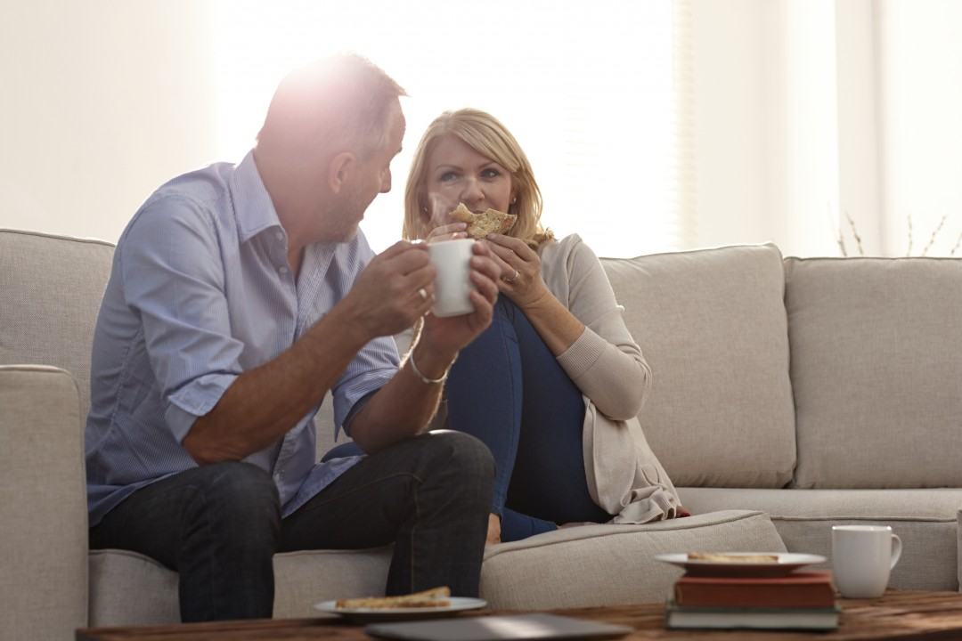 Portrait of mature couple talking in living room with coffee while at home