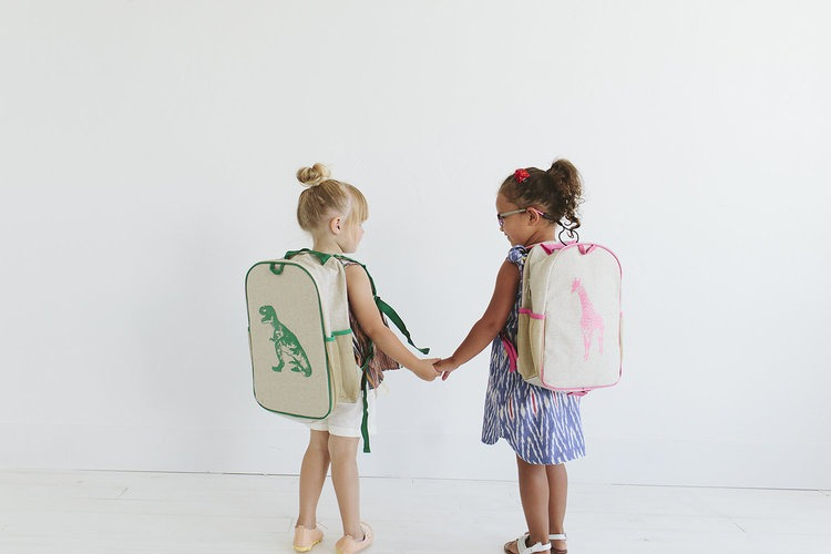 two young girls holding hands wearing So Young backpacks