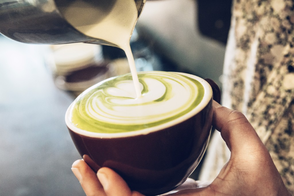 Barista pouring a green tea latte