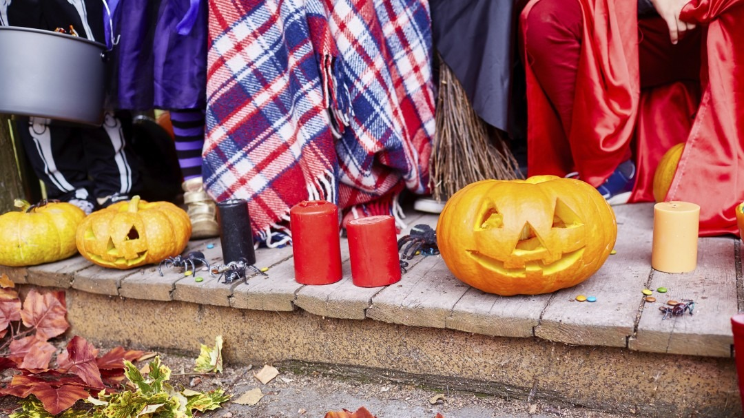 Close-up of children's legs, candles and pumpkins