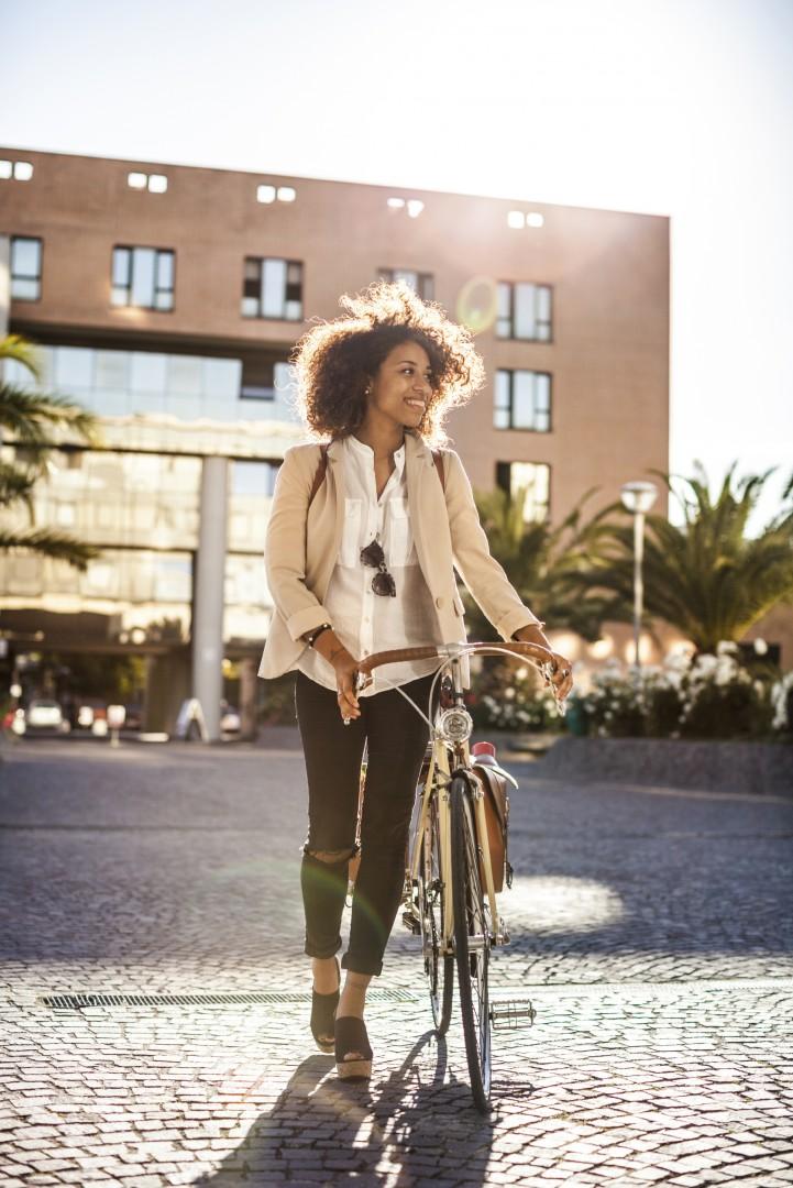 Business woman walking with bike