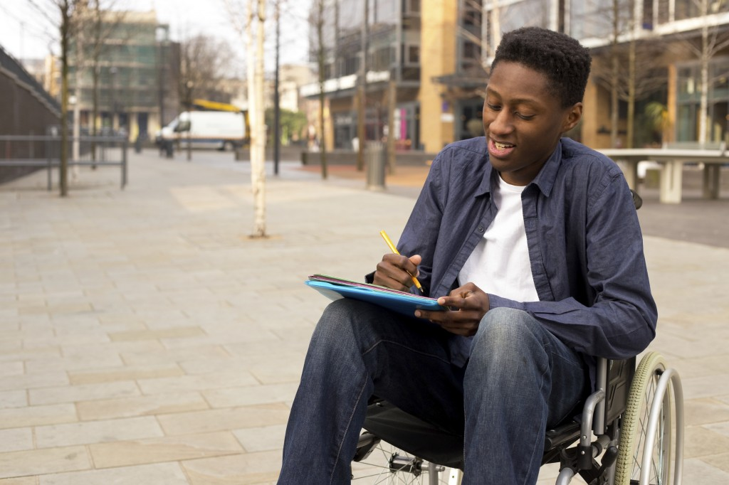 young man in a wheelchair writing a letter