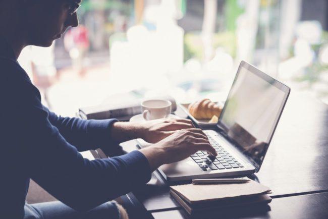 Freelancer working on laptop when having breakfast