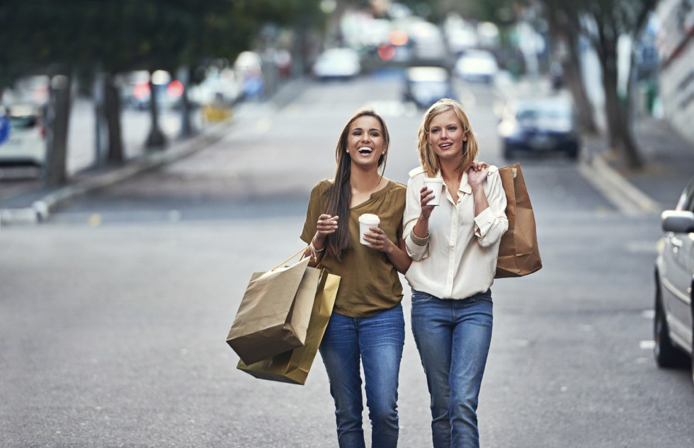 Two friends walking down the street with shopping bags