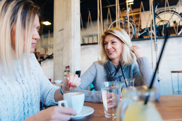 middle aged woman having coffee with her daughter