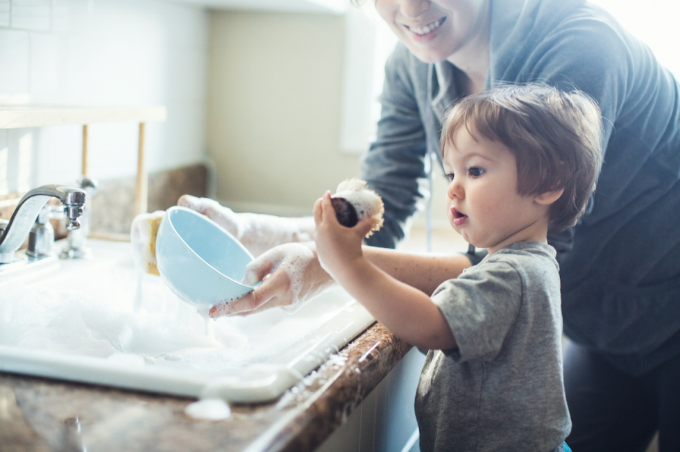 baby doing dishes with his mom