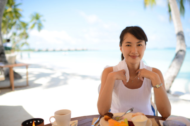 Woman Eating Healthy After Workout on Beach