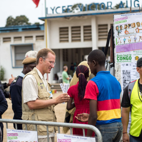 Photo Credit Catherine Murphy; Keith BRINKMAN (USA), Programs Administrator, Gives Tickets To Each Person Who Walks Through The Gate On Selection Day In Pointe Noire, Congo