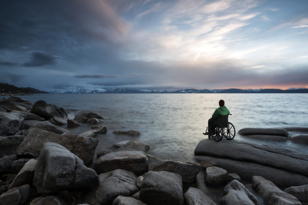 man in wheelchair looking at mountains