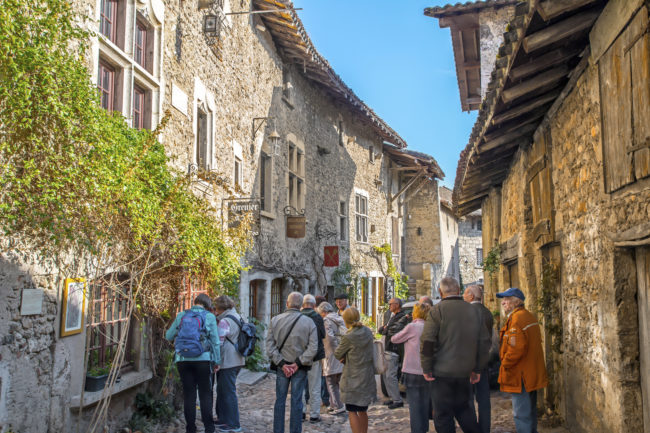 Perouges, France - September 29, 2015: Small group of people, majority of mature age, probably a group of retirees during an organized trip, men and women are visiting old streets of the medieval town of Perouges in Ain, Rhone-Alpes region in France (Europe). The facades of ancient buildings are in stone, and there are some sign of market for those tourist and for tourism in general (like bakery (boulangerie), restaurant etc...). This outdoor picture was taken during a sunny day at the beginning of the autumn season.