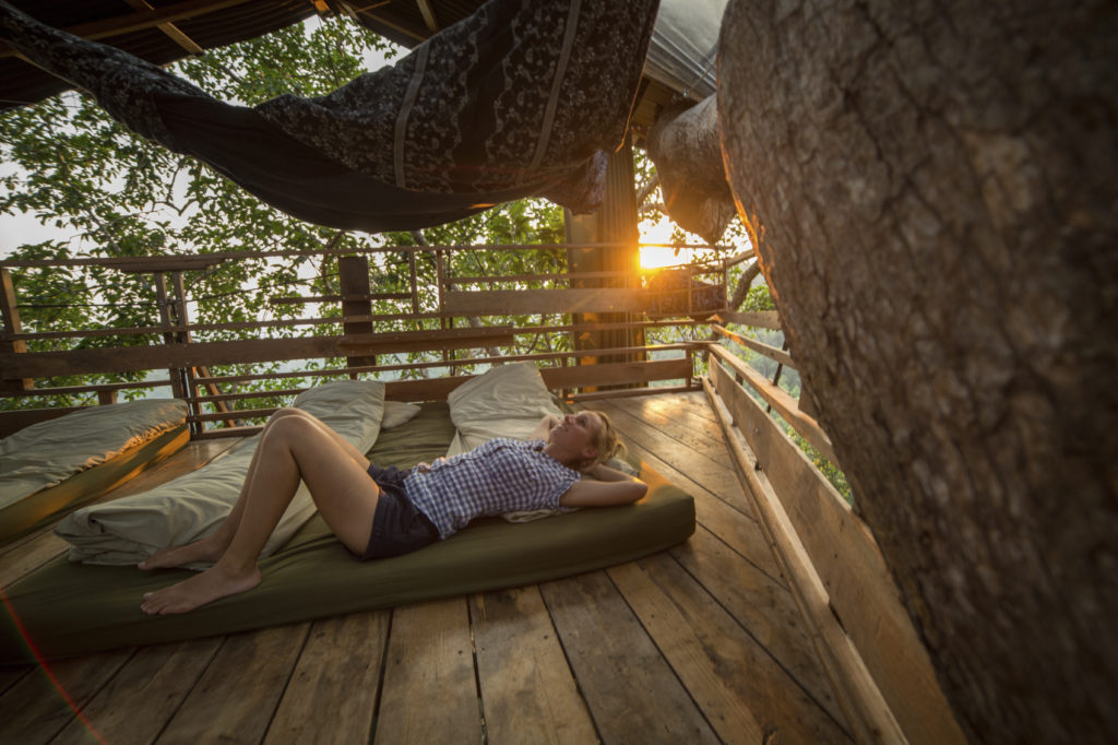 Woman laying in a treehouse