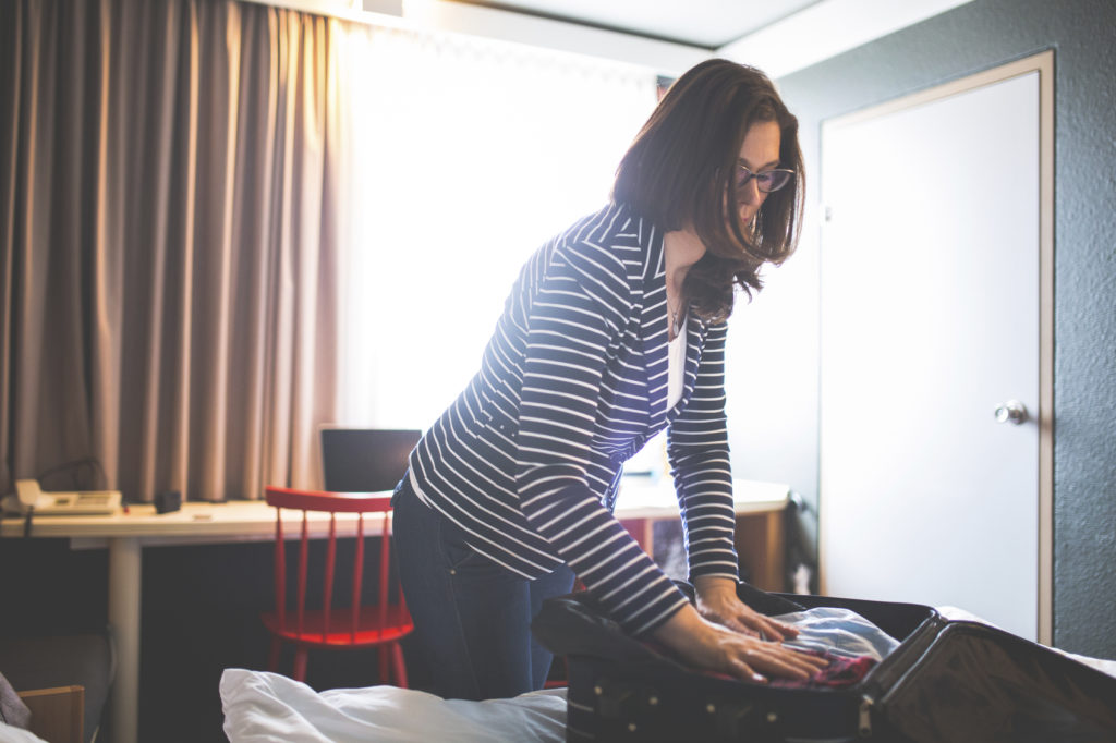 Woman packing for a trip in hotel room