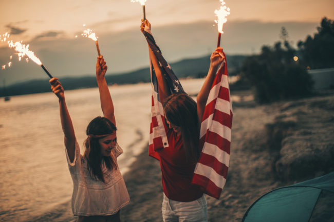 Young hipster girls at the beach, celebrating the fourth of July - by holding an American flag and fire torches up high