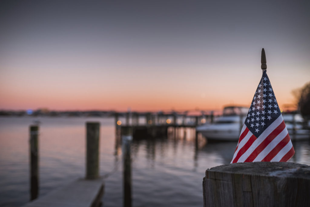 An American Flag pictured over the Potomac River looking towards Washington DC, picture taken in Alexandria, Virginia.