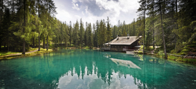 Wide view of an amazing lake surrounded by the forest. The location is Cortina d'Ampezzo (Veneto, Italy) in the Dolomites mountains during the summer season.