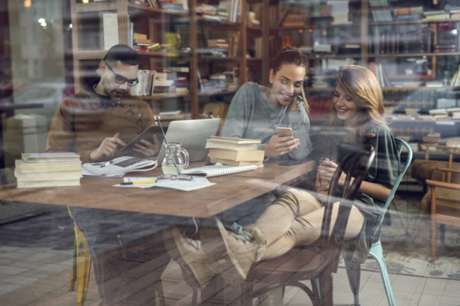 Group of college students sitting in the library and using wireless technology. Man is using digital tablet while women are using cell phone. The view is through glass.