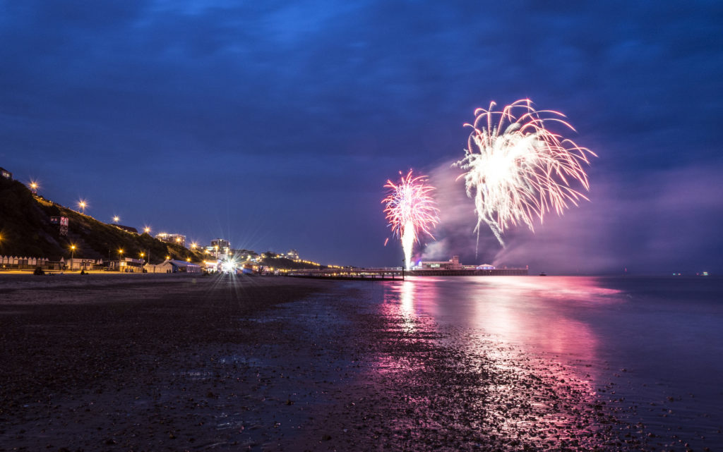 Fireworks display from Bournemouth Pier in Dorset. Popular tourist destination, Bournemouth beach in the foreground.