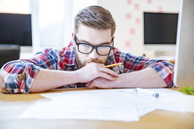 Thoughtful bearded young man in glasses working with blueprits using pencil and ruler in the office