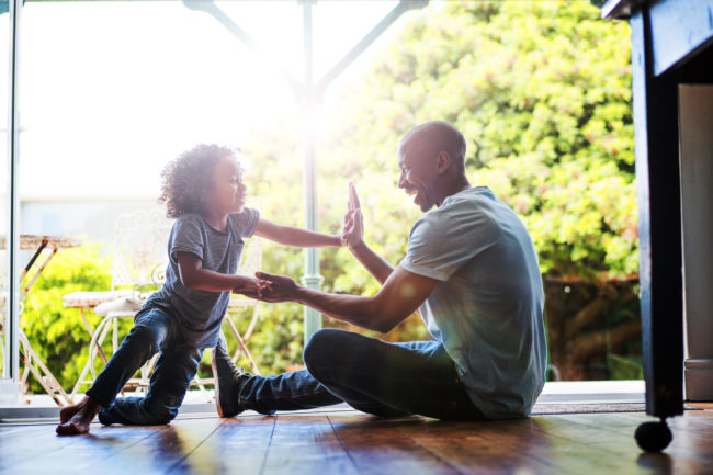 A photo of happy father and son playing on floor. Smiling boy touching man's hands. They are sitting at the entrance of house.