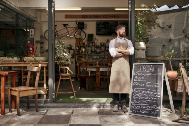 Portrait of a young man standing in front of his coffee shop. Young man with beard wearing an apron standing with her arms crossed and looking away.