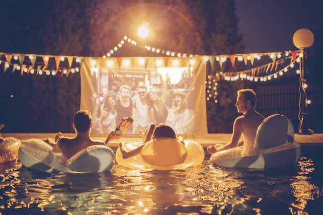 Young Friends Having Pool Movie Night Party Floating On The Inflated Mattresses And