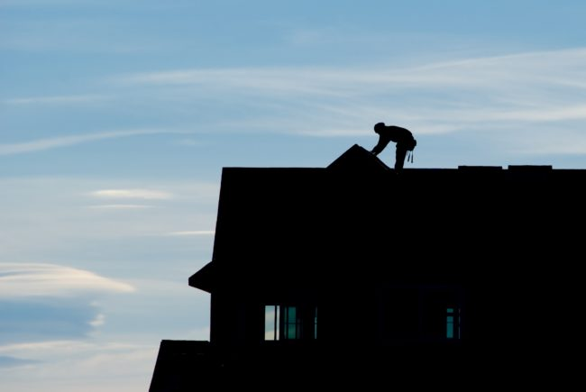 Silhouette of roofer working on peak of roof against blue evening sky.
