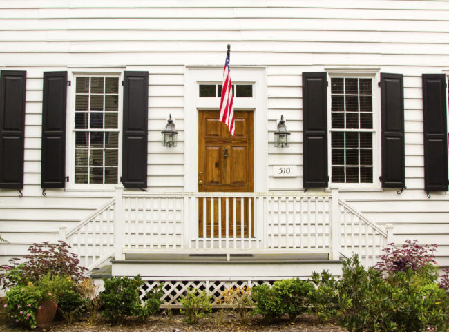 brown wooden door in white wall with US flag