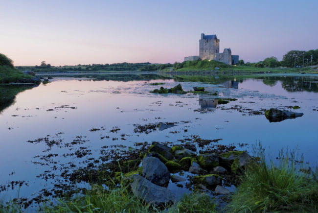 Dunguair Castle reflected in the still waters of Galway Bay at Sunset. Ireland.