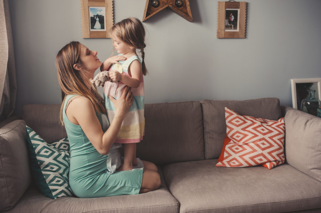 happy mother and toddler daughter playing together at home, casual lifestyle in real life interior
