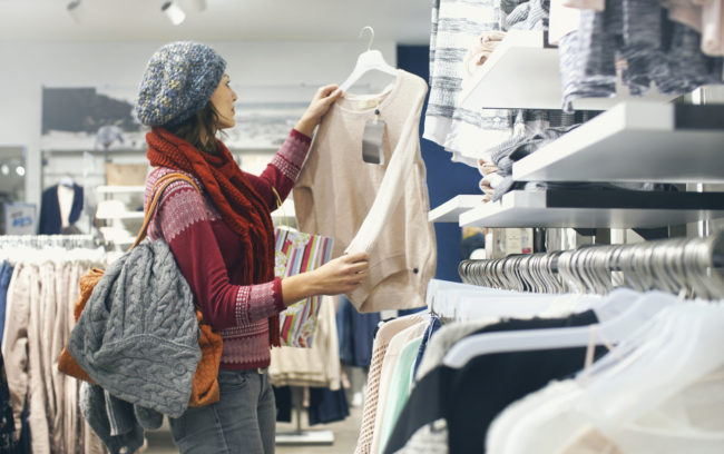 Closeup of smiling blond woman choosing clothes at department store in local supermarket. She's holding a beige blouse and looking at it. The woman is wearing gray cap, red sweater and scarf. Side view.