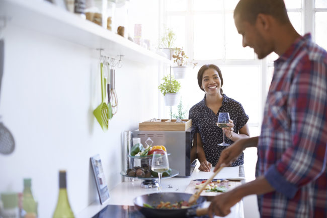 Shot of a young couple enjoying cooking dinner together in their kitchen