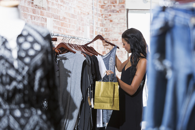 A stylish young woman shopping in a clothing store, looking at clothing hanging on a rack. She is holding a hanger, looking down at a shirt. She is mixed race, African American and Caucasian, with long, black hair.