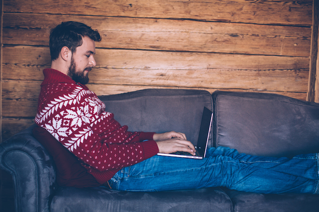 Man sitting on sofa in wooden cabin. Wearing Christmas sweaters. Enjoying in the warmth of his home for Christmas. Using his laptop to chack his mail or some work. Austrian Alps. Wooden wall in background.