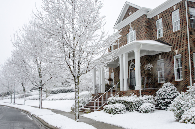 A traditional, brick home during a Winter snow storm. The architecture reflects old styles, however, the construction of the homes has used modern materials and finishes. Nice image for any Winter project.