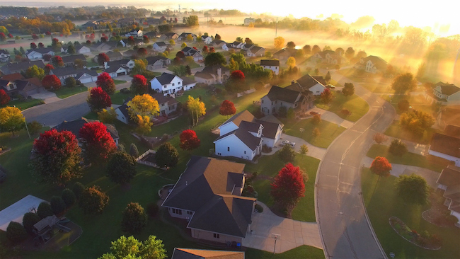 Magical sunrise over sleepy neighborhood with shadows and sunbeams, through ground fog, aerial view.