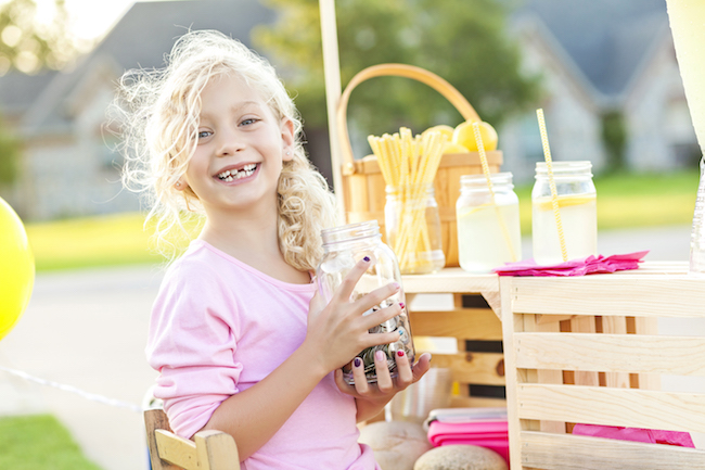 Adorable little girl with curly blond hair. She is smiling a big toothy smile at the camera. She has a jar of coins and cash that she has earned while selling lemonade. There are cups of lemonade and straws behind her. There is even a basket full to the top of lemons. The little girl is alone, she is wearing a light pink shirt.