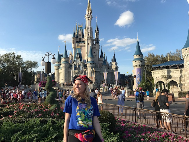 Girl standing in front of Magic Kingdom at Disney World
