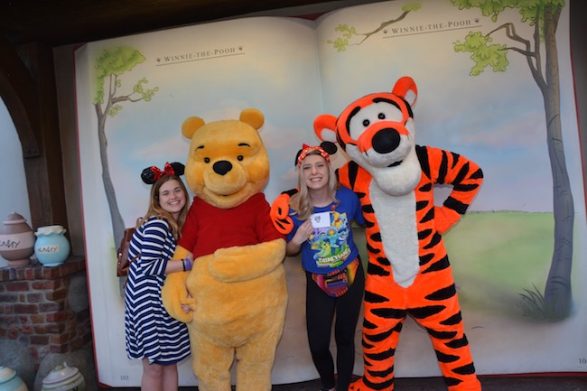 People standing with Winnie the Pooh and Tigger at Disney World