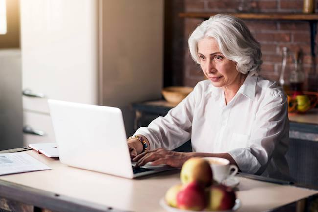 Retired woman working from home on laptop