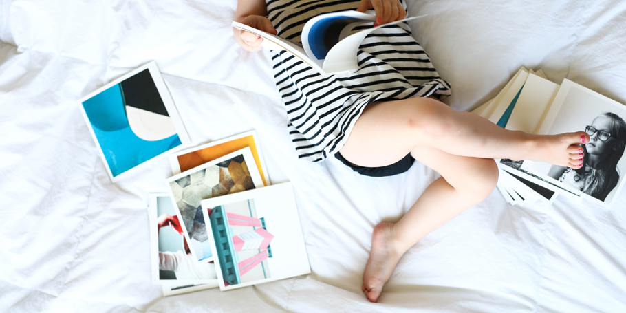 Child laying on bed looks at photo books