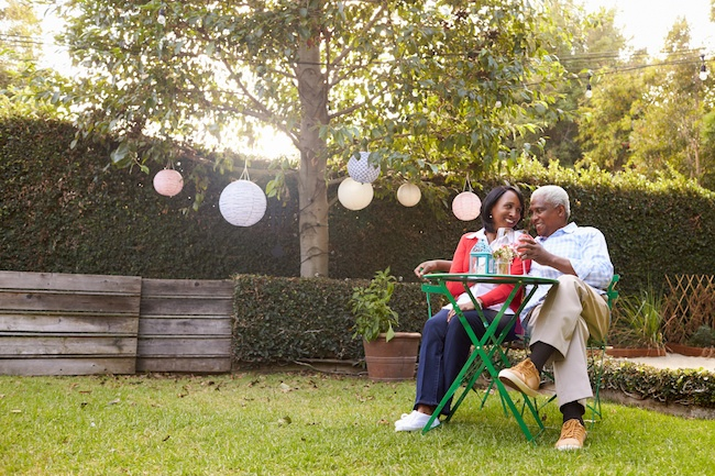 Elderly couple sitting in their backyard enjoying a glass of wine