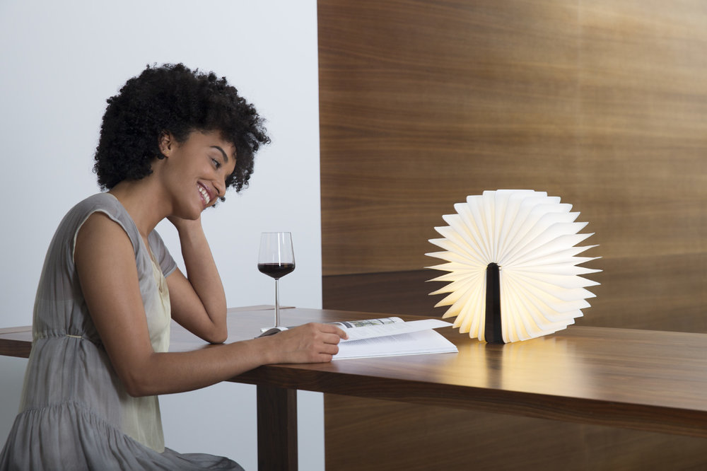 woman reading and drinking wine next to a lumio light