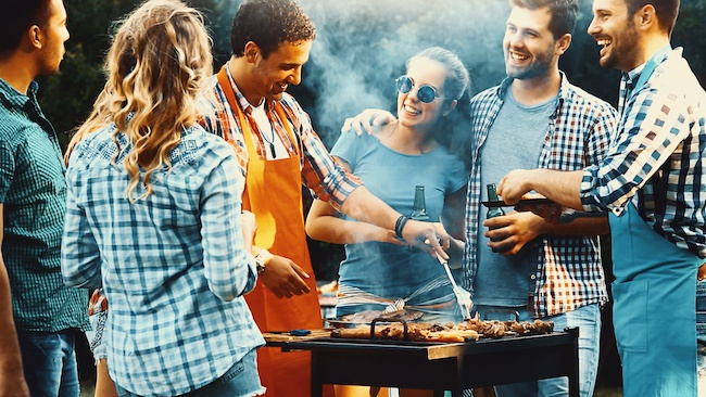 A group of friends gathered around a grill