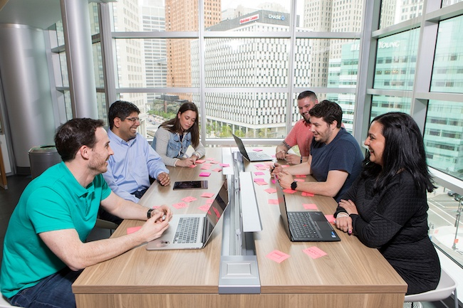 Group of team members gather around an office table