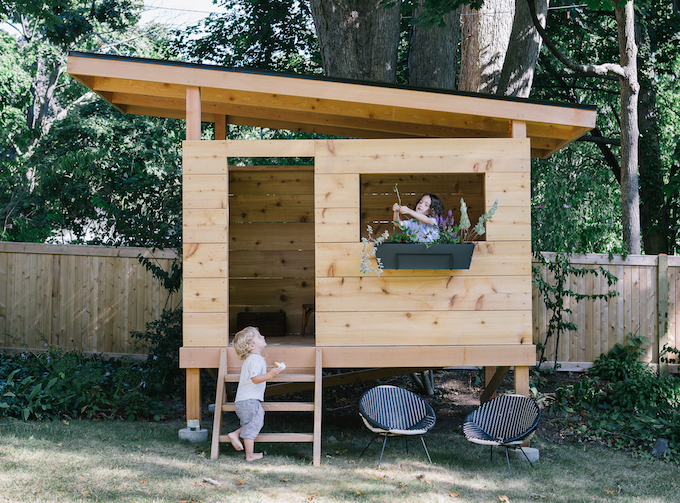 Two children play in a playscape house